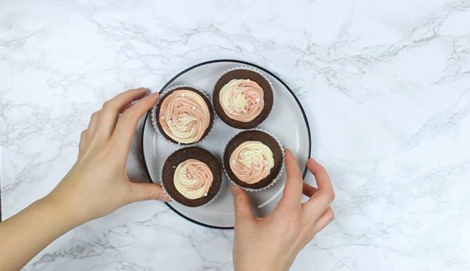 overhead shot of 4 candy cane cupcakes on a plate with a hand touching one