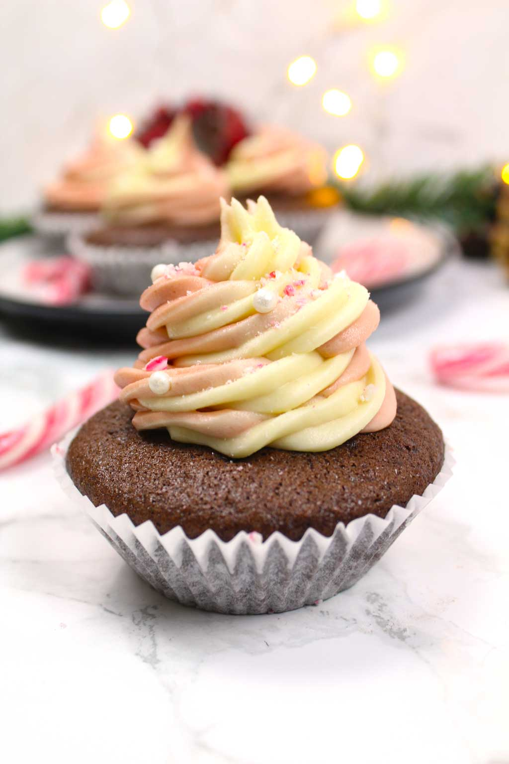 a candy cane cupcake with buttercream frosting on top