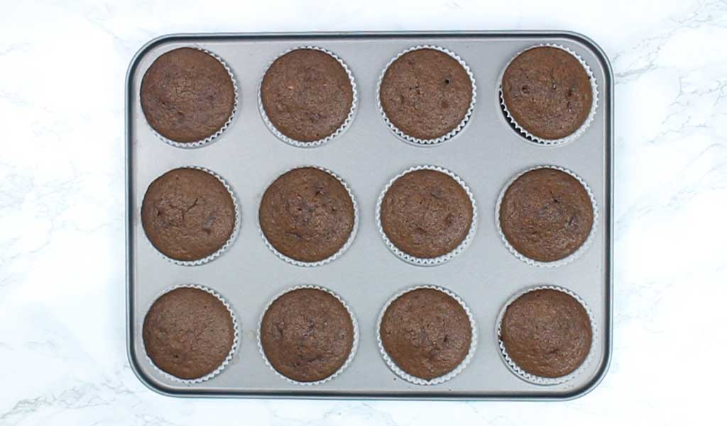 chocolate cupcakes cooling in a cupcake tin