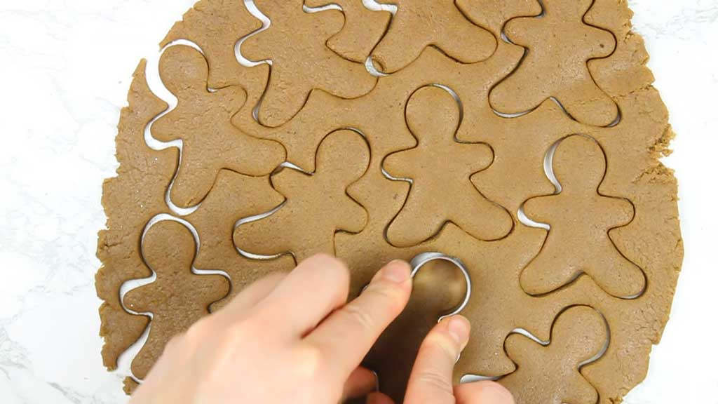 cutting gingerbread man shapes out of the rolled out dough
