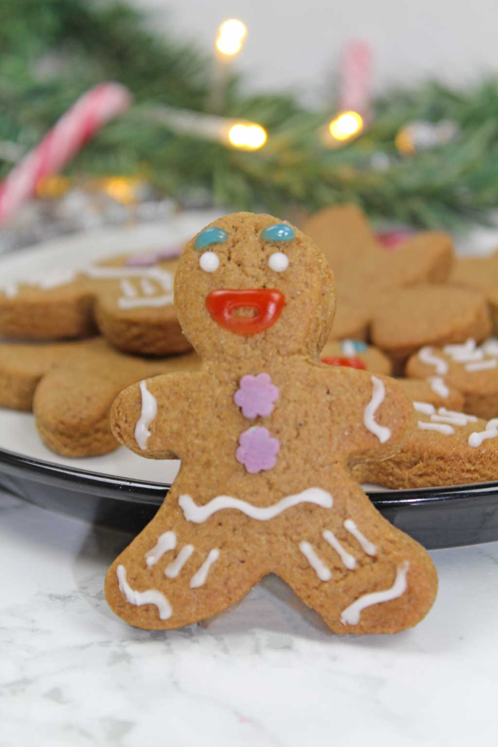 gingerbread man standing in front of a plate of gingerbread men