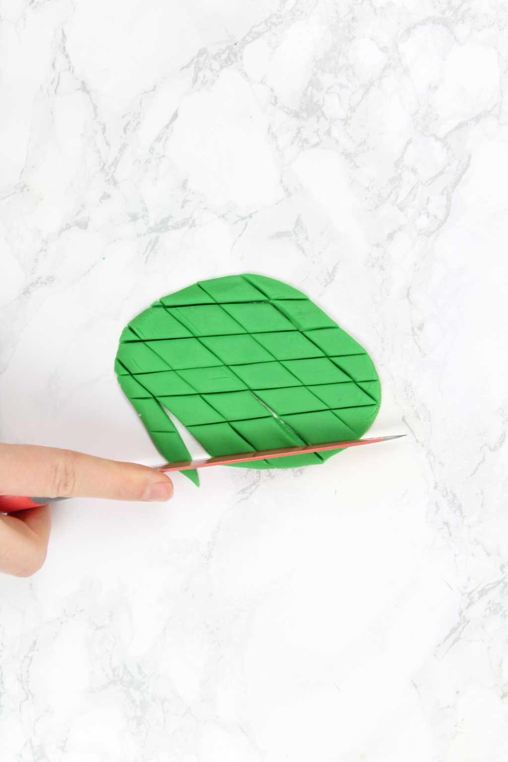 cutting diagonal lines into green fondant