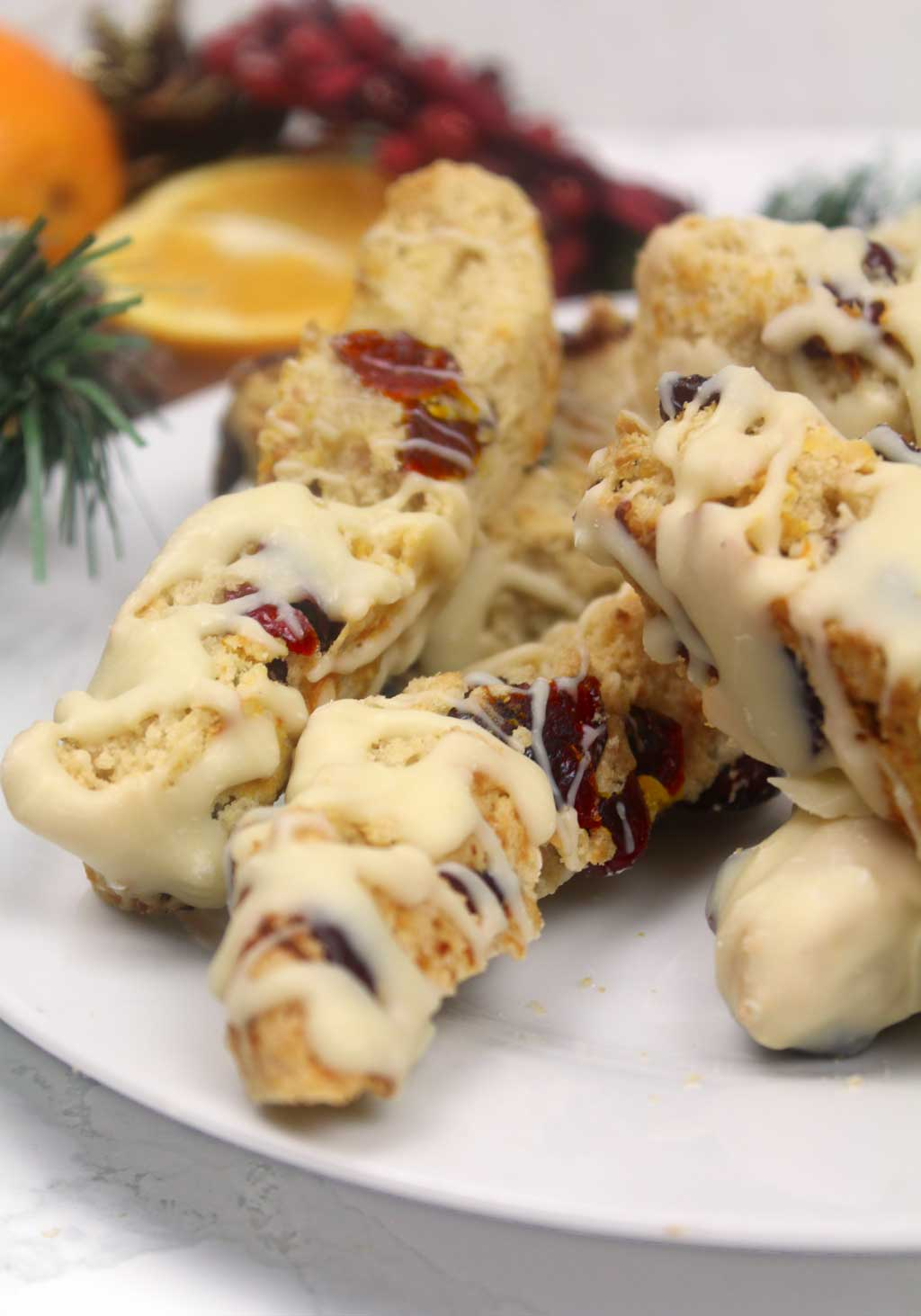 orange and cranberry biscotti on a plate with oranges in the background