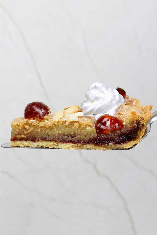 slice of vegan bakewell tart with whipped cream and cherries on top