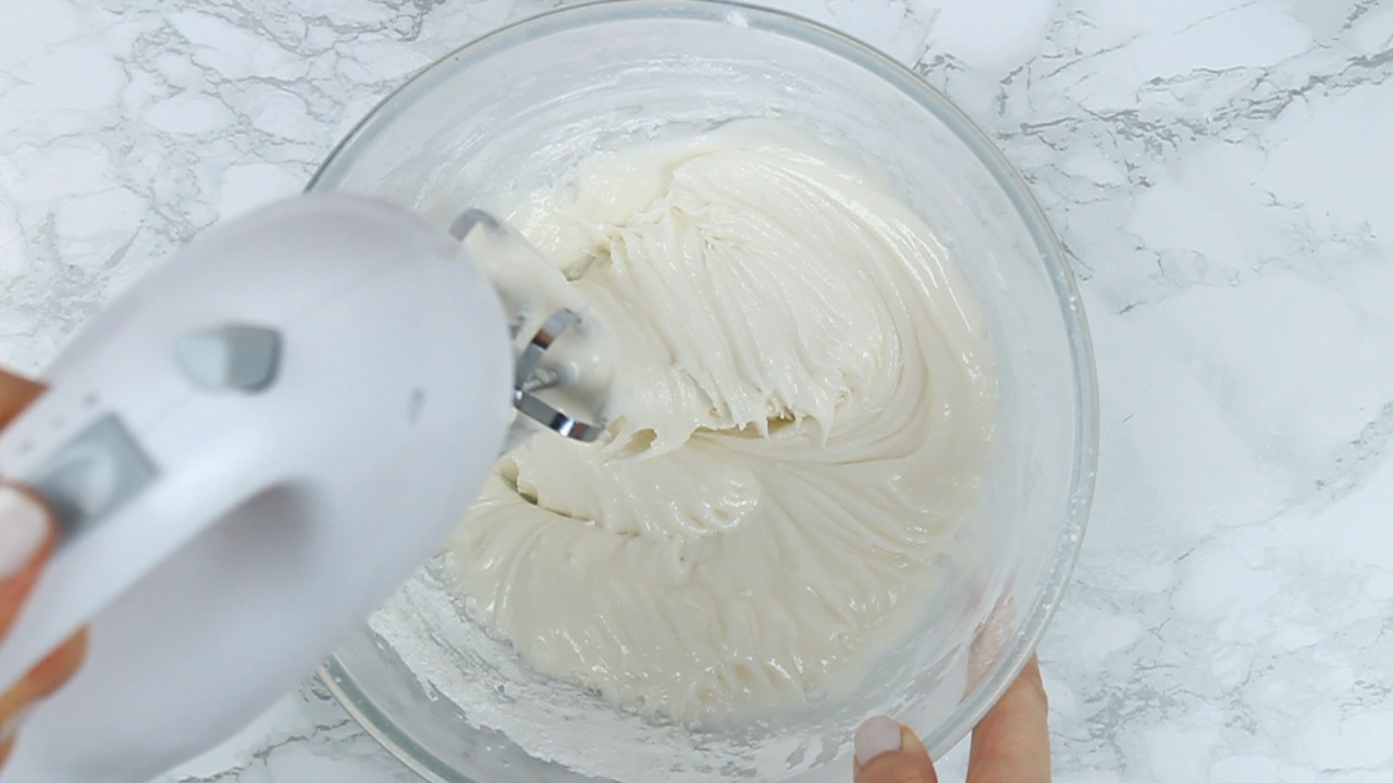 whisking vegan royal icing with an electric hand whisk
