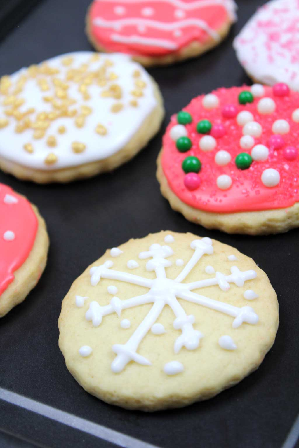 a batch of cookies on a tray with royal icing and sprinkles on top