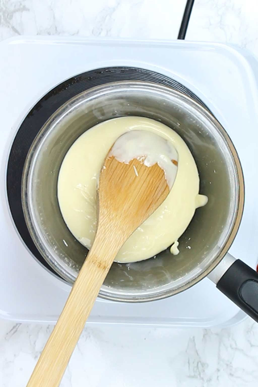 melted white chocolate in a pot with a wooden spoon in