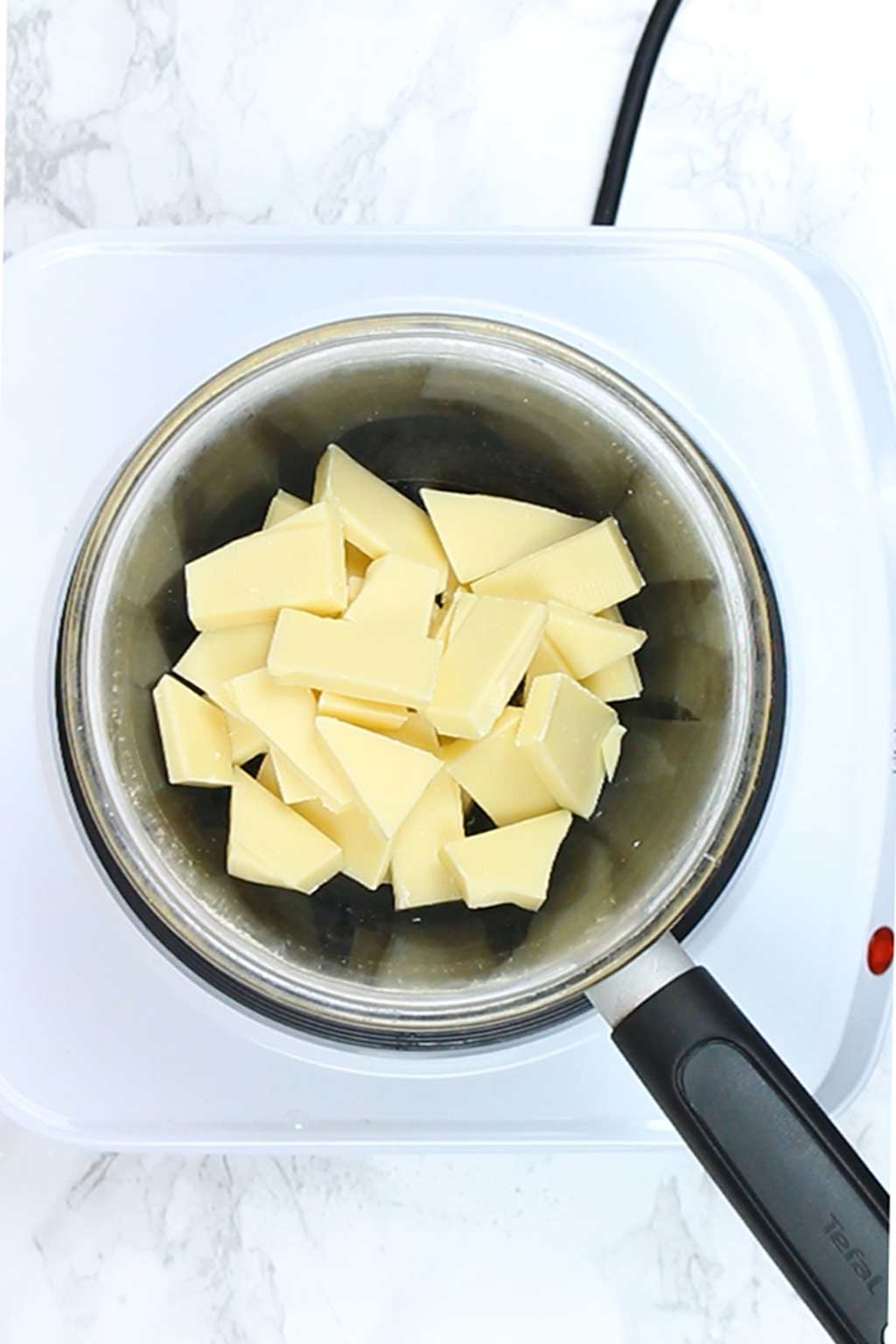chopped white chocolate in a bowl over a pot of simmering water