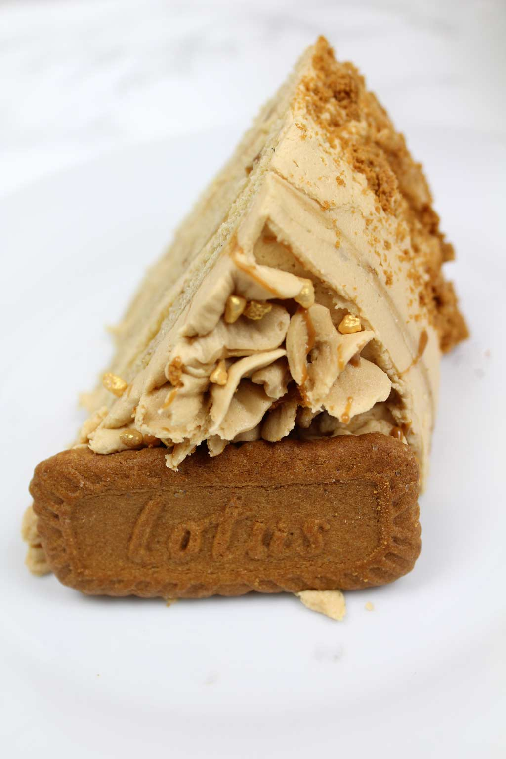 a slice of vegan Biscoff cake on a plate with a Biscoff cookie on top