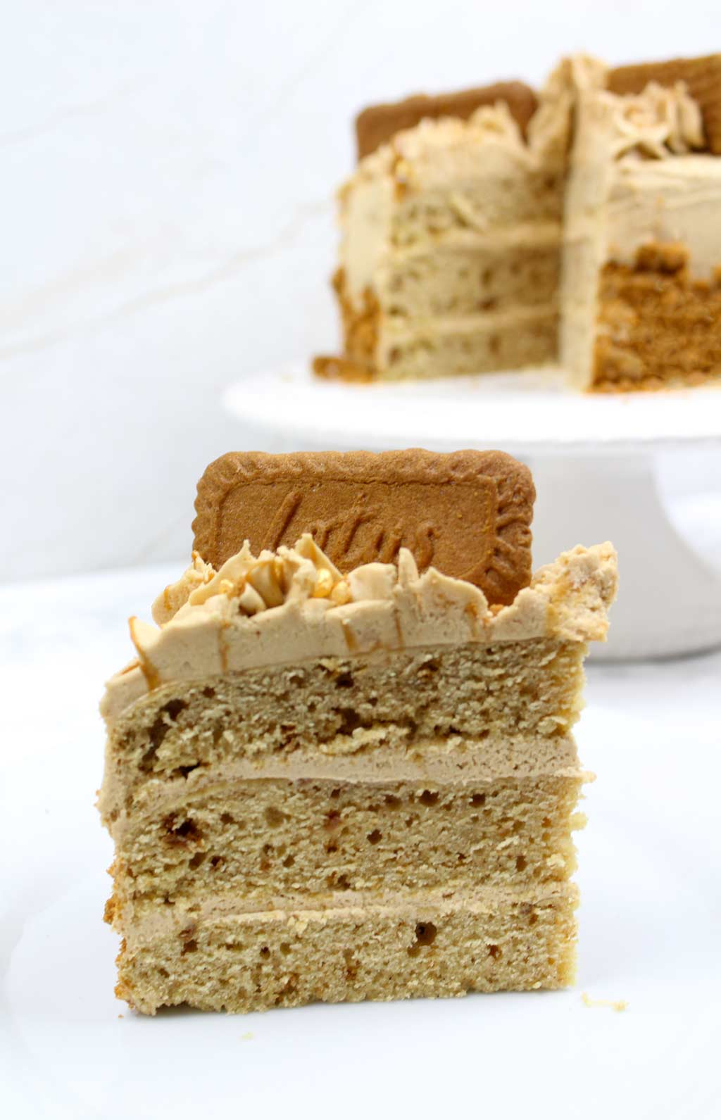 a slice of biscoff cake with the rest of the cake behind it on a cake stand
