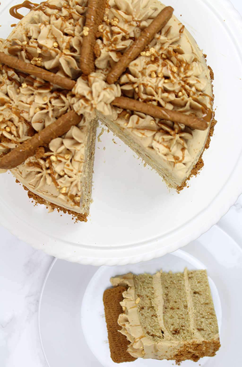 overhead shot of vegan biscoff cake. One slice is on a plate and the rest is on a cake stand beside the plate