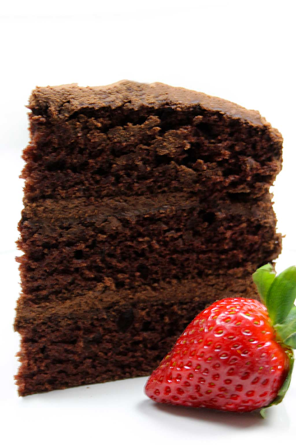 a slice of chocolate cake with a strawberry beside it
