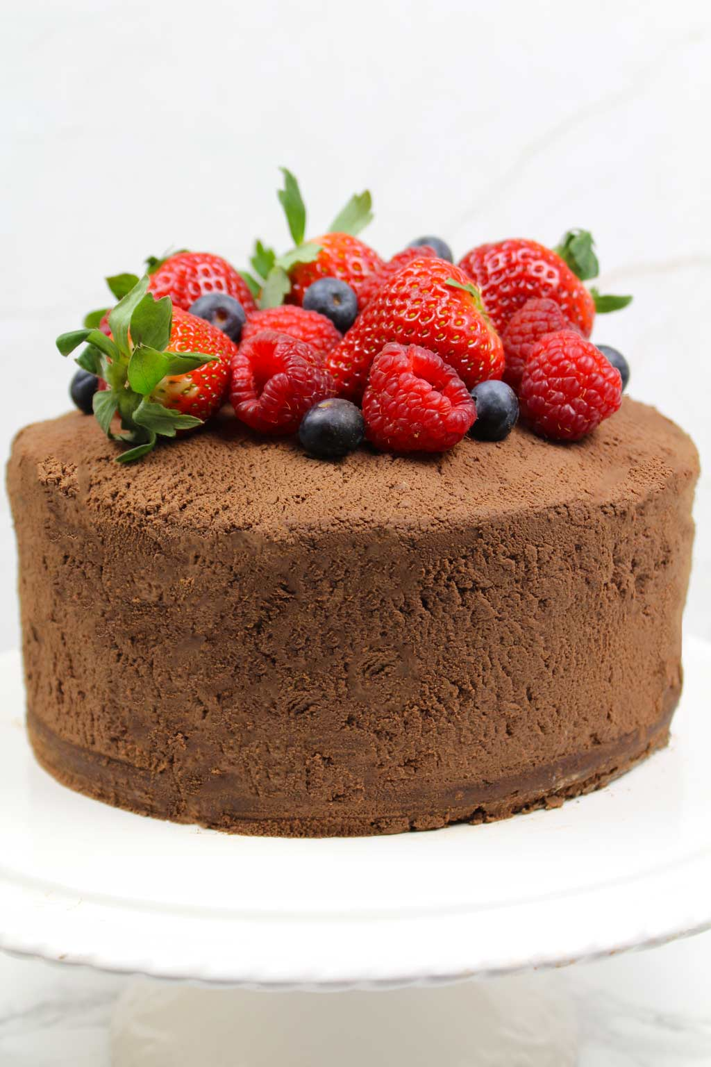 whole chocolate cake with frosting all over and berries on top