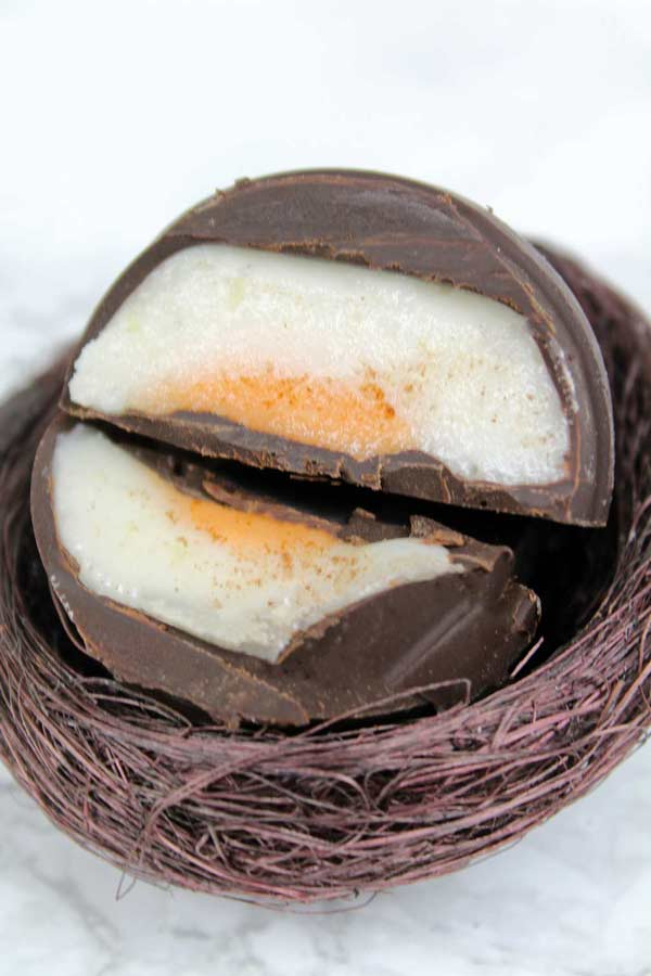 two halves of a vegan Creme Egg with the fondant in the center showing