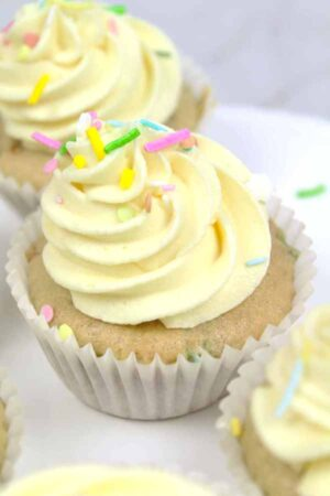 vanilla cupcake with frosting and colourful sprinkles on top