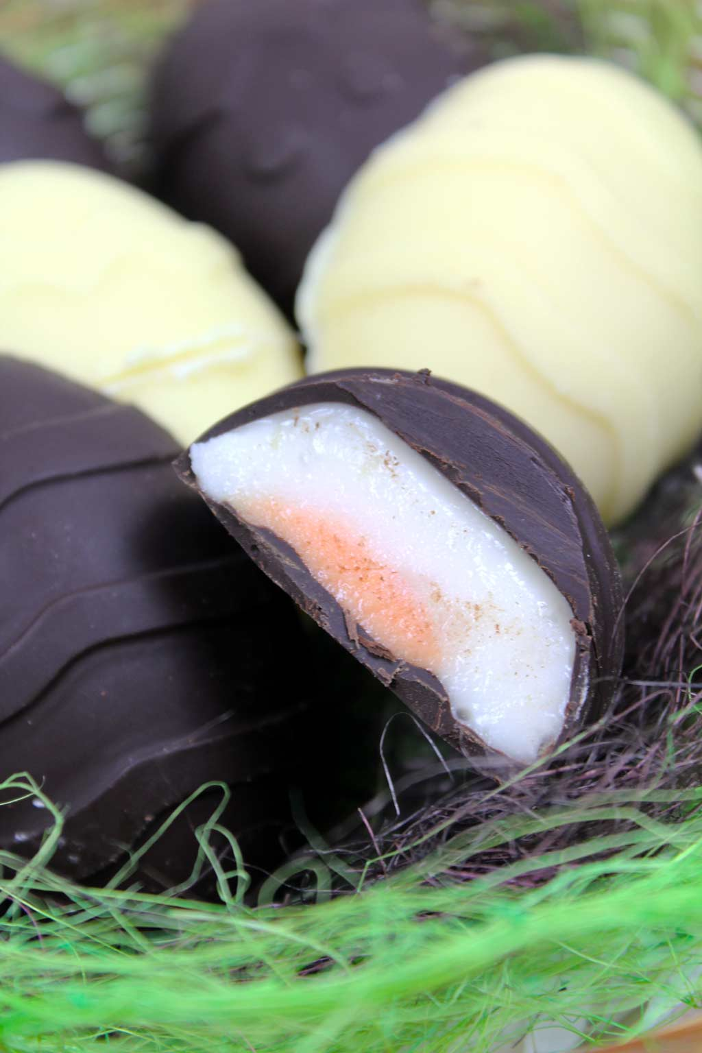 A basket full of vegan creme eggs. One at the front is cut in half to show the fondant filling.