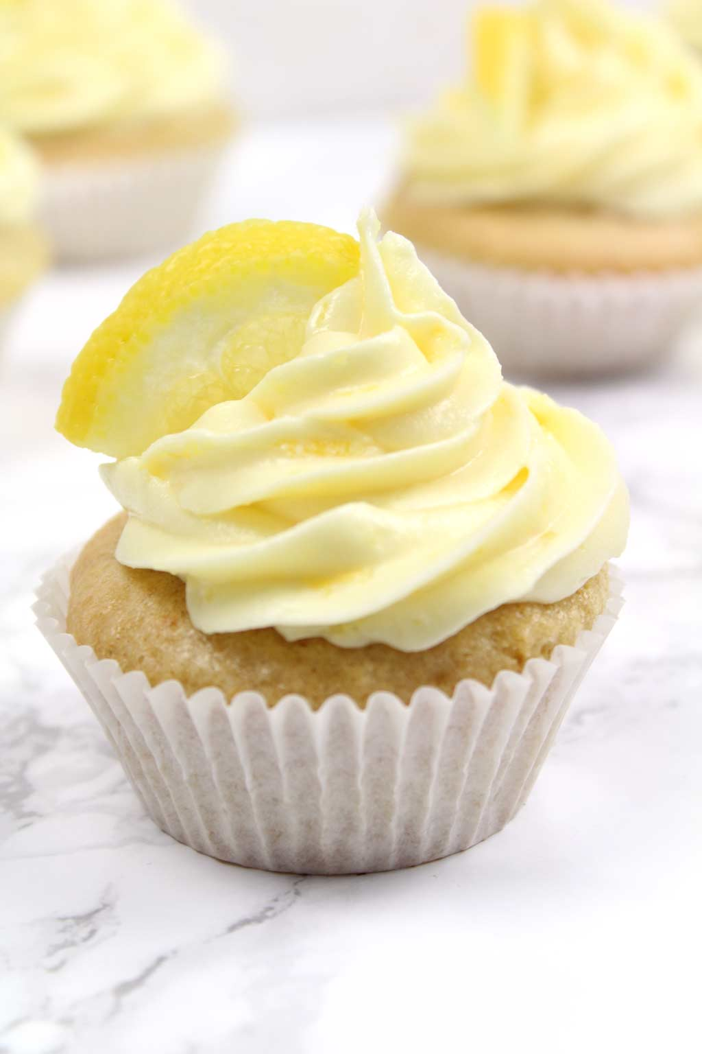 close up of a lemon cupcake with frosting on top