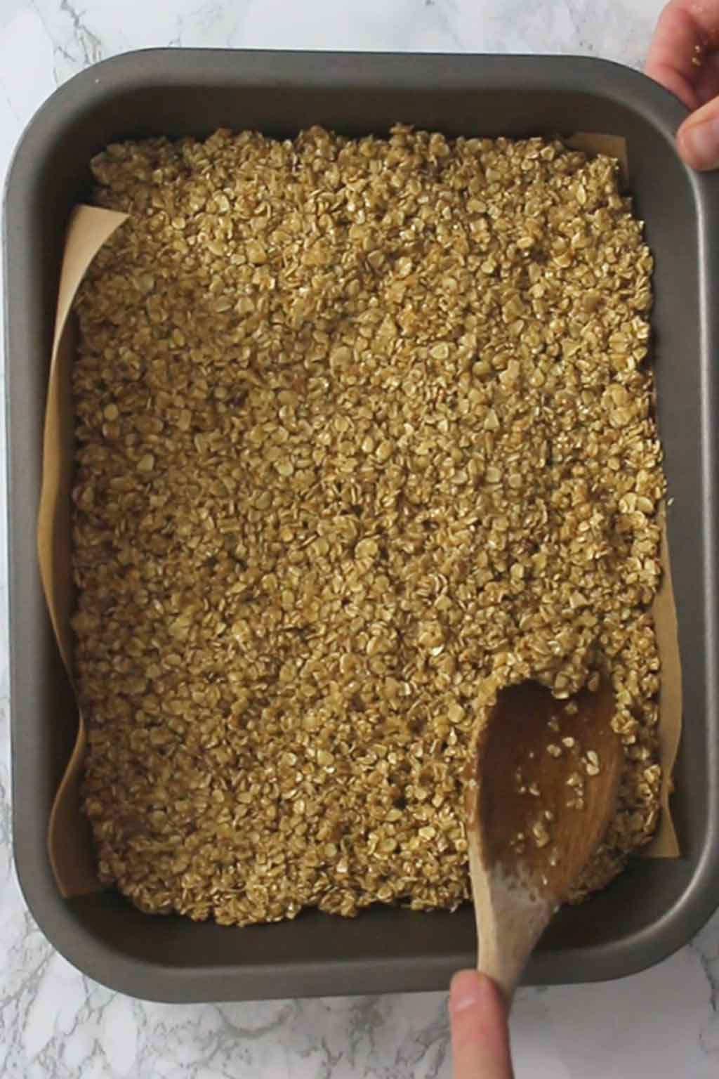 Packing flapjack mix into the tin
