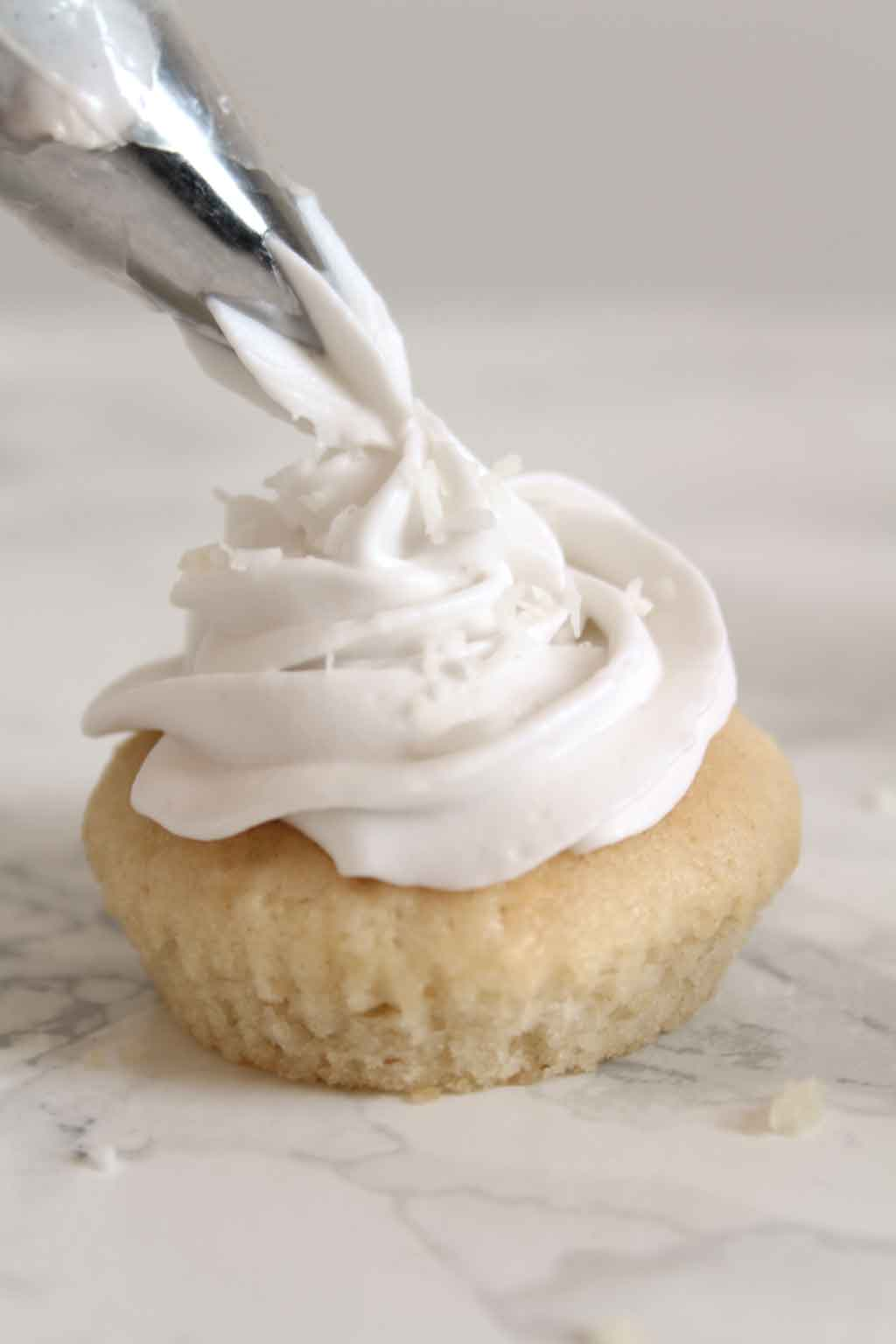 Piping vegan whipped Cream Onto A Cupcake