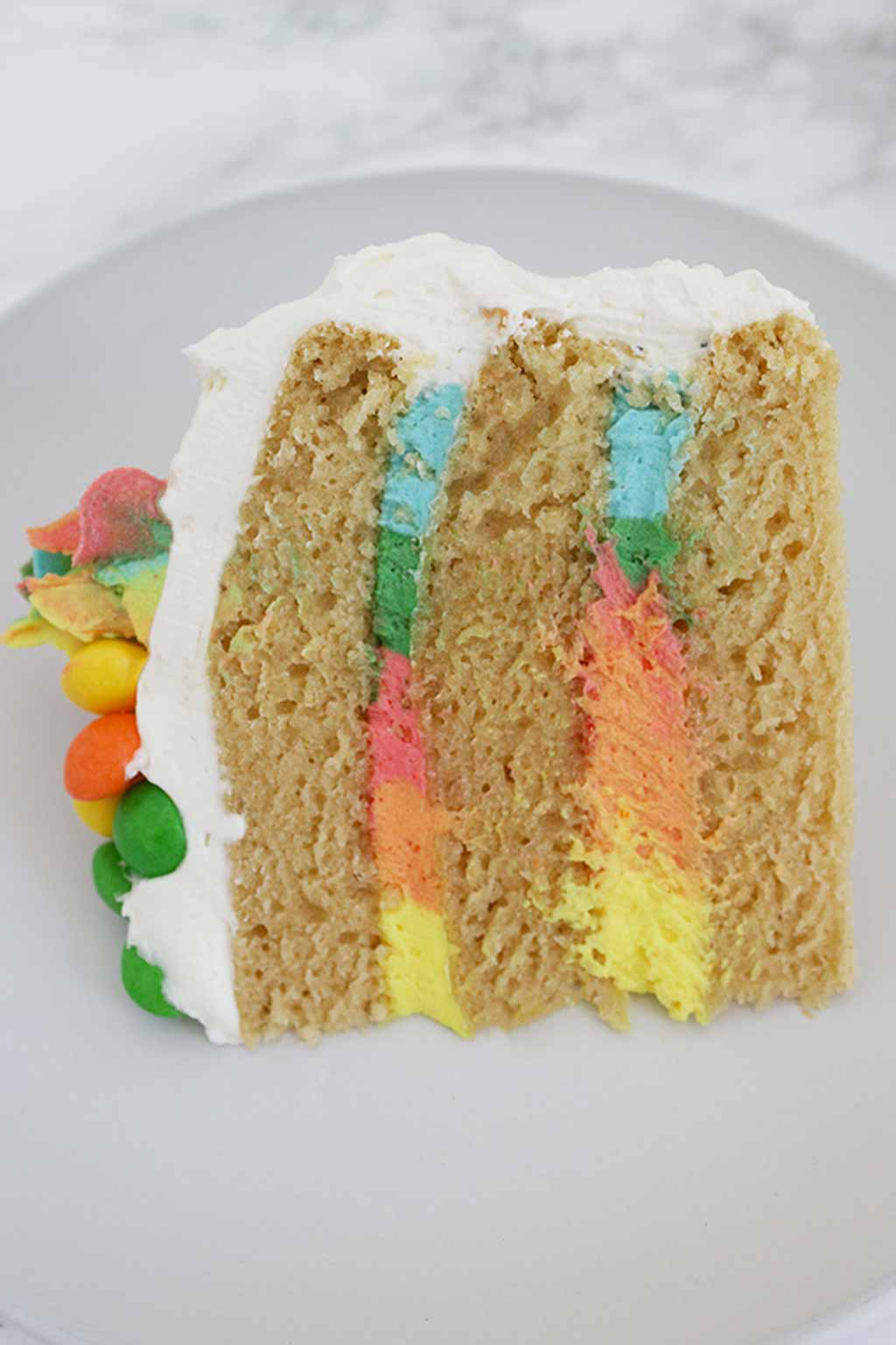 Rainbow Cake Slice with frosting showing in the middle
