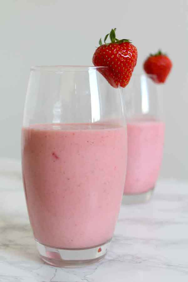 two strawberry milkshakes in glasses with a strawberry sitting on the rim of each glass