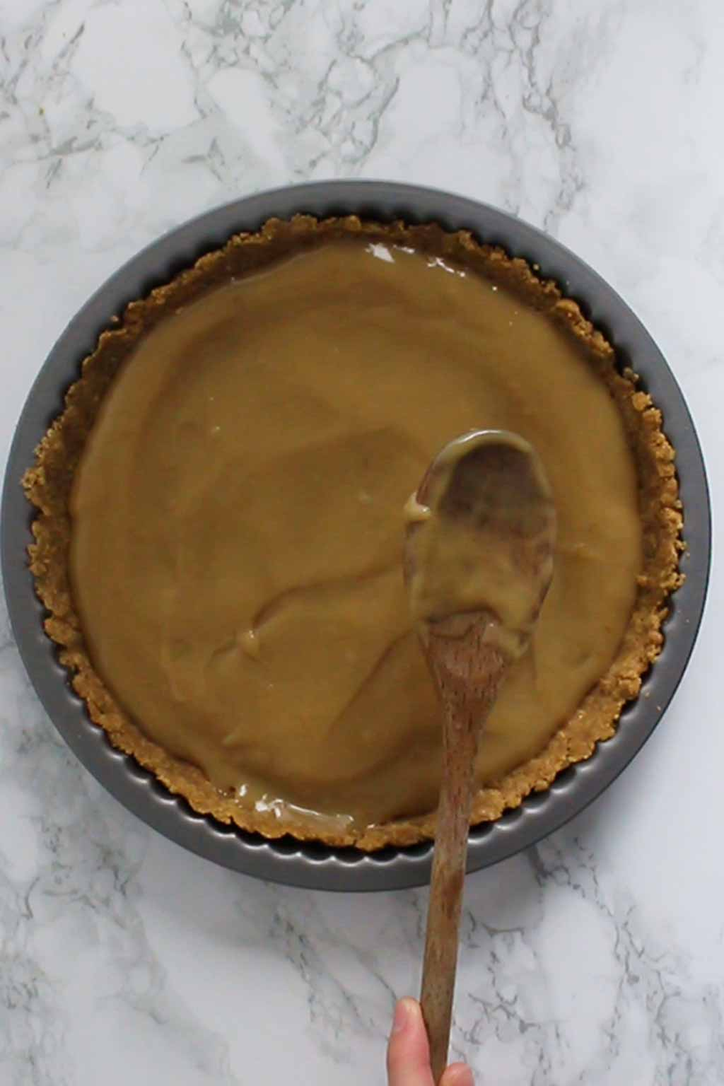 Spreading Caramel Onto Biscuit Base