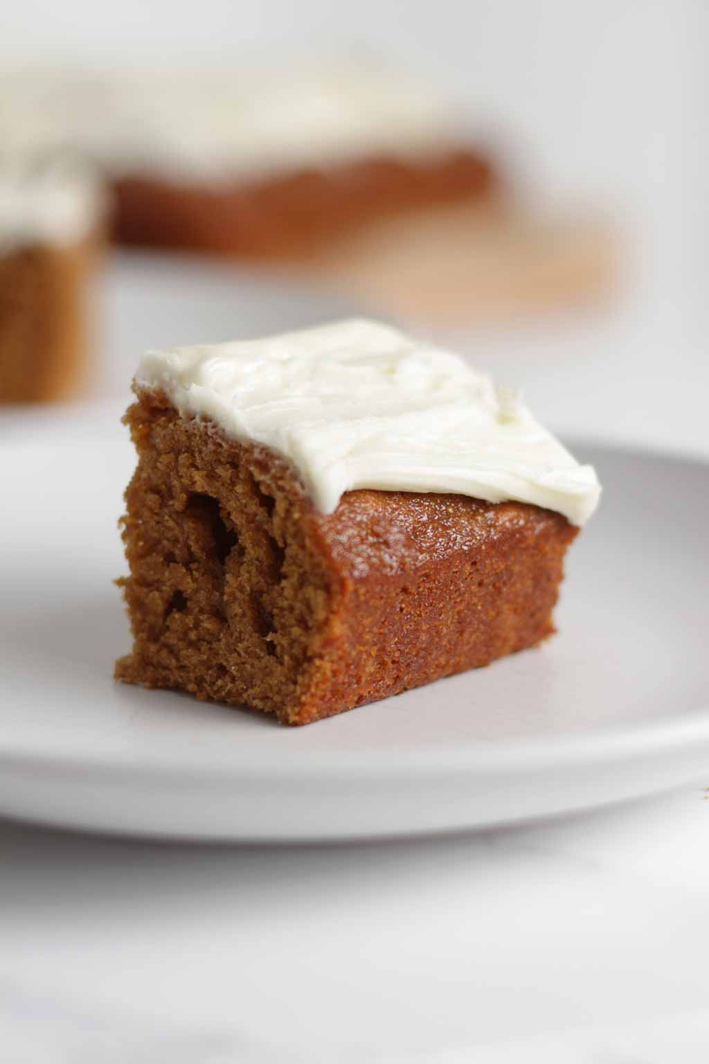 slice of vegan Ginger Cake on a plate with icing on top