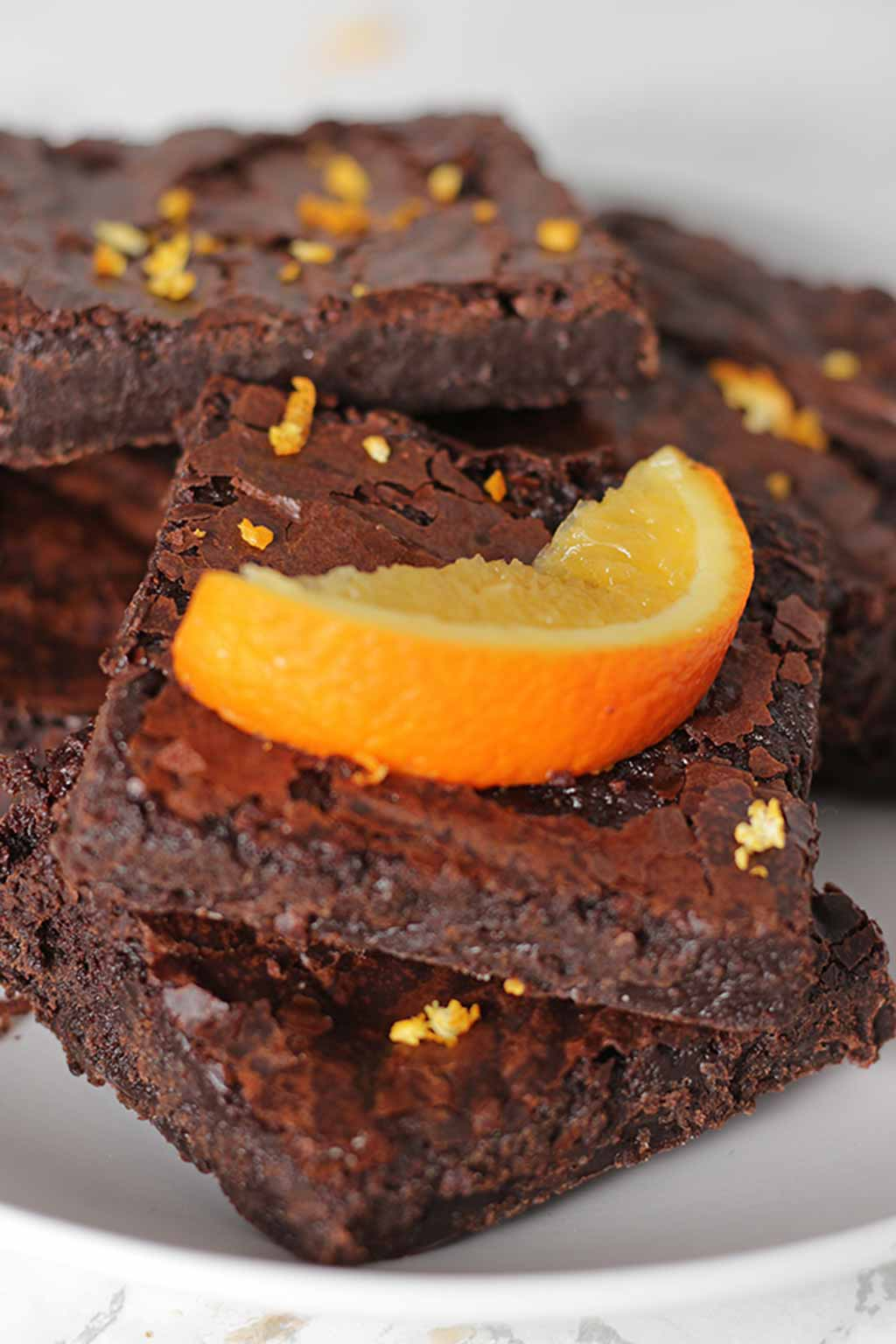 A Pile Of Chocolate Orange Brownies With An Orange Wedge On Top
