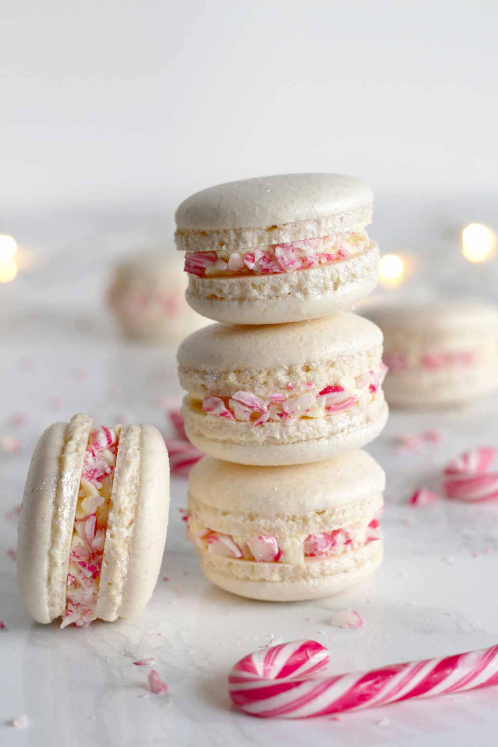 3 macarons stacked on top of one another behind a red and white candy cane