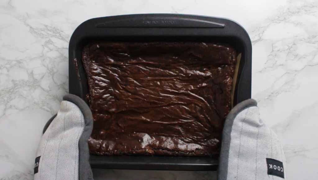 Gloved Hands Holding The Tray Of Baked Brownies