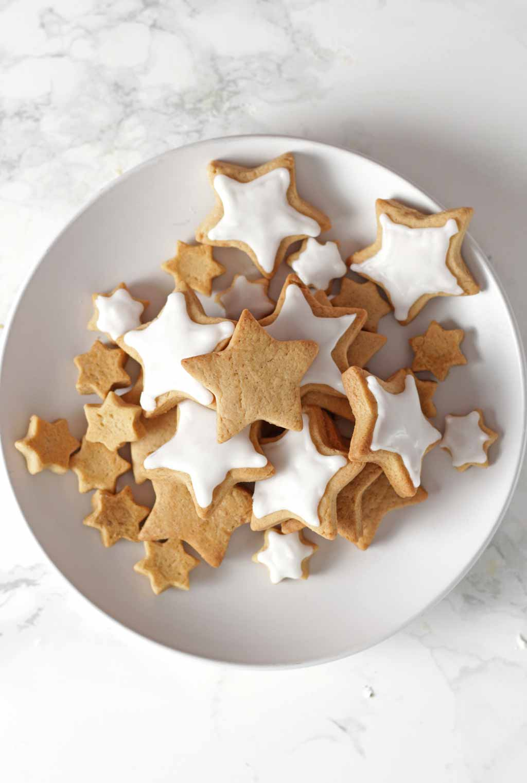 Overhead Shot Of Star Shaped Cinnamon Cookies On A White Plate