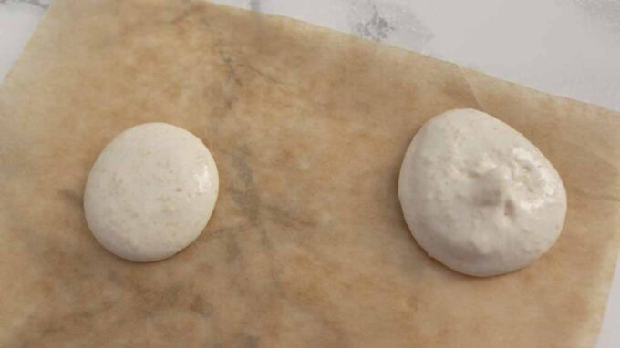 Two Macarons On A Sheet Of Baking Paper. The left one is ready and the right one is undermixed.