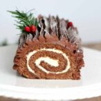 Vegan Chocolate Yule Log with red berries and a green sprig on top