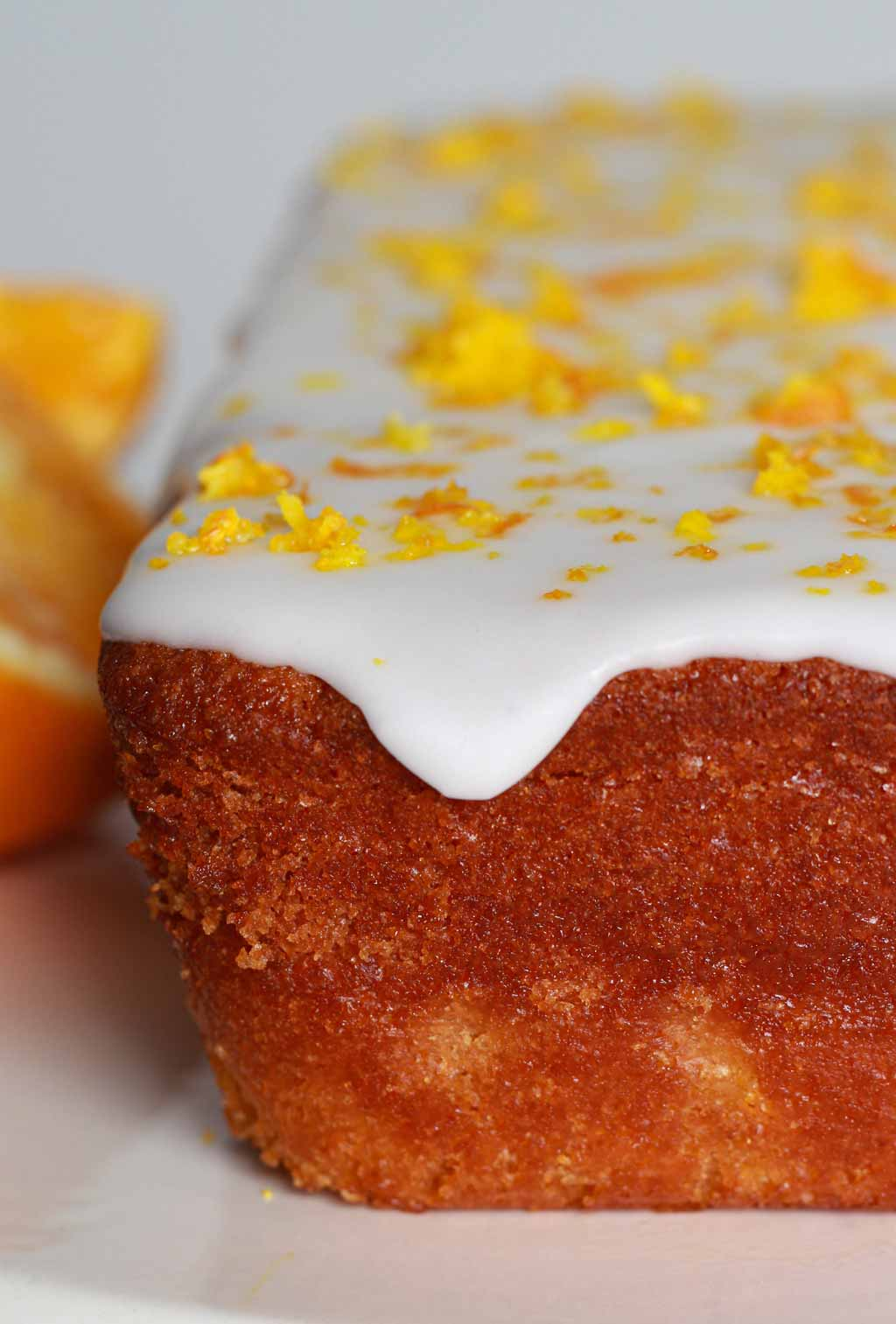 Close Up Of Orange Cake With Icing Dripping Down The Side