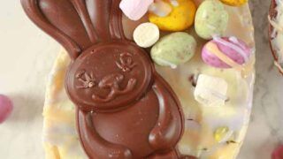 a chocolate bunny on top of a white cheesecake filled Easter egg