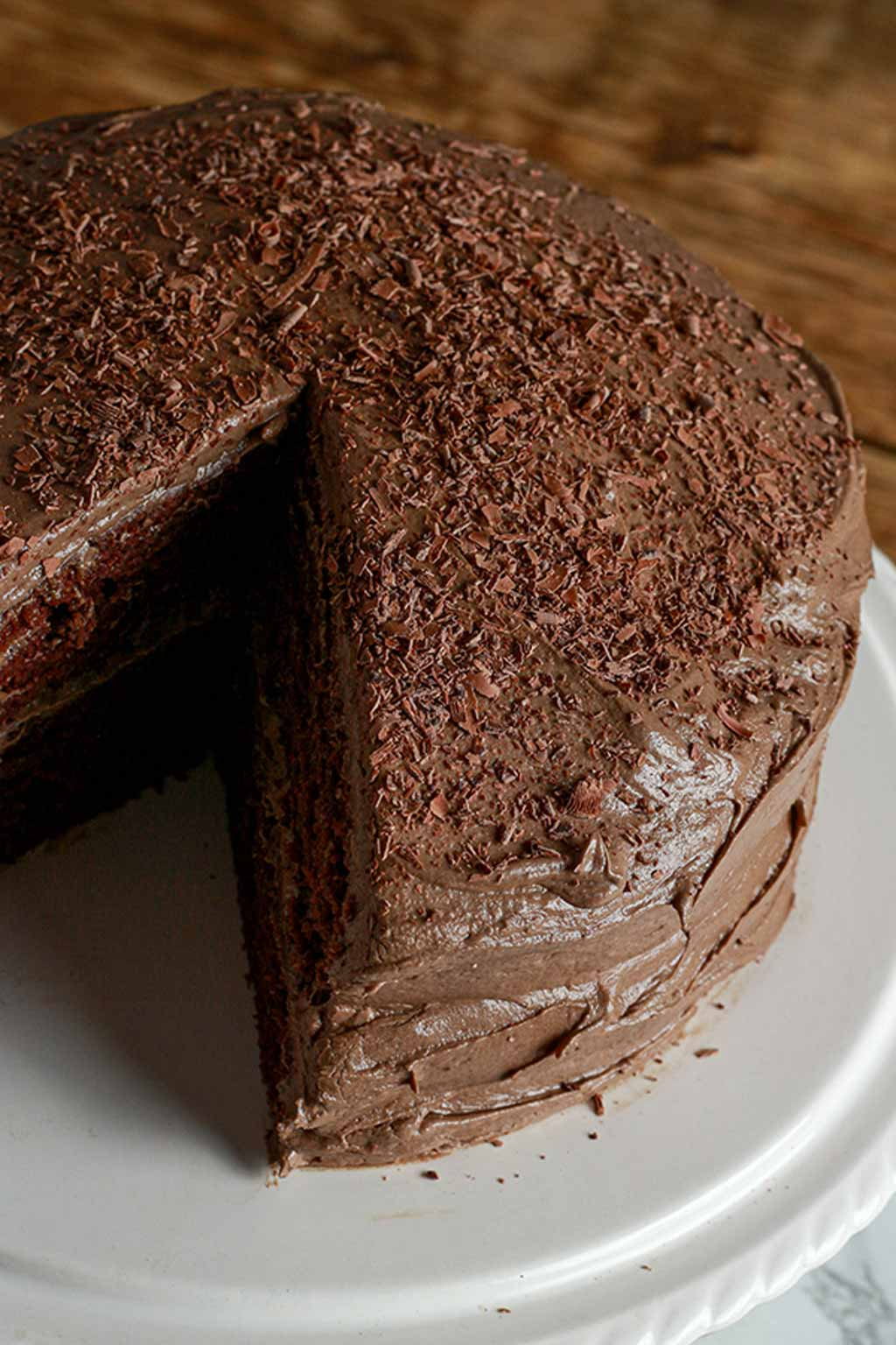 Vegan Chocolate Fudge Cake On A White Cake Stand With 1 Slice Missing