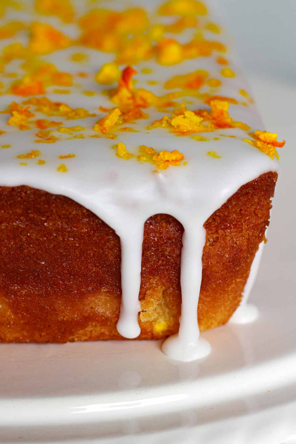 close up of Vegan Orange Cake with white icing dripping down the side
