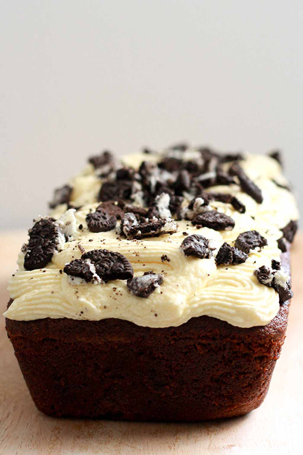 chocolate loaf cake with icing and crushed Oreo cookies on top
