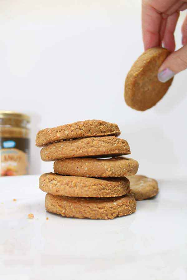 a peanut butter cookie being removed from a stack of cookies