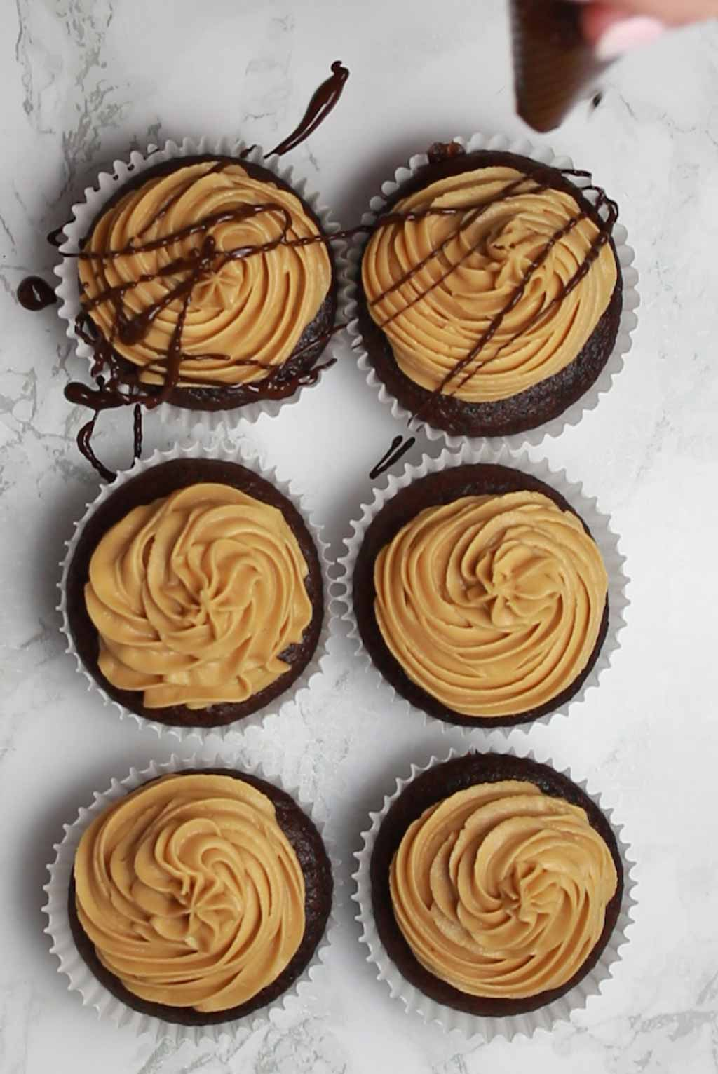 Drizzling Chocolate Over The Cupcakes