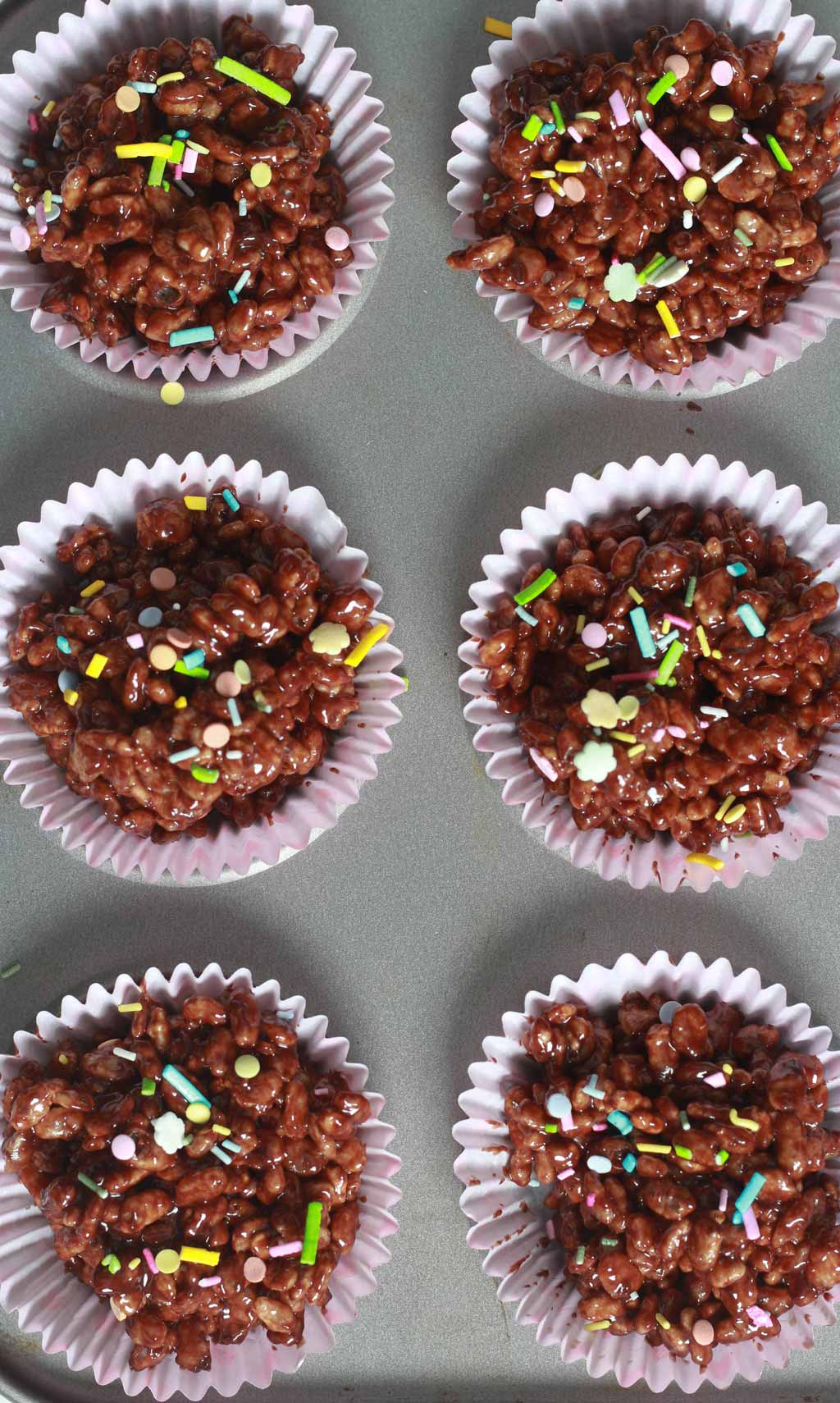 Wet Chocolate Crispy Cakes with sprinkles on top In Cupcake Tin